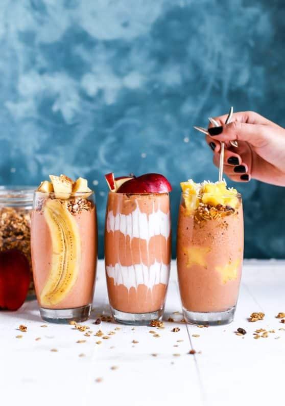 Três copos de smoothies e cereais espalhados em frente a eles. Uma mão branca com unhas pintadas com esmalte preto segura um canudo de metal, posicionado dentro do terceiro copo à direita. À esquerda, uma maça à frente de um pote transparente com cereais.